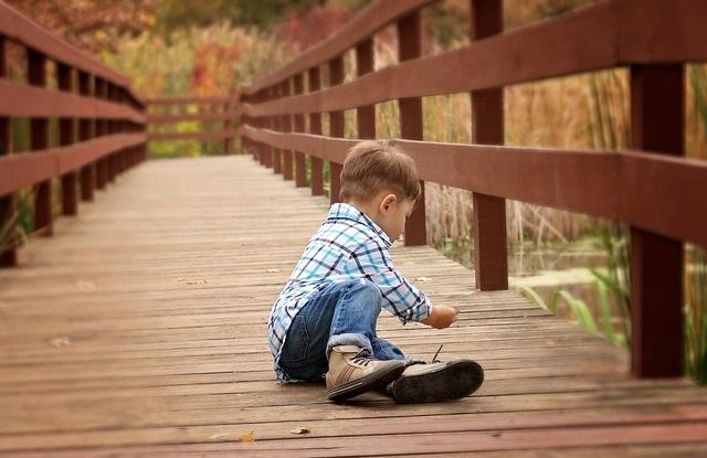Chłopiec bawiązy się na pomoście