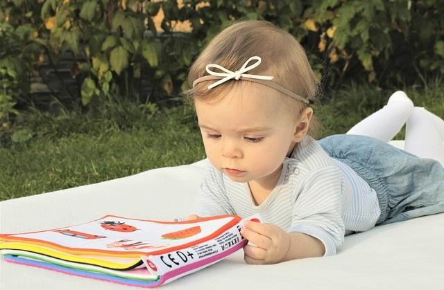 Leżące dziecko z książeczką