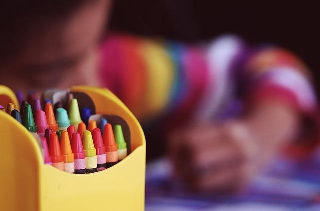 Kredki i rysujące w tle dziecko